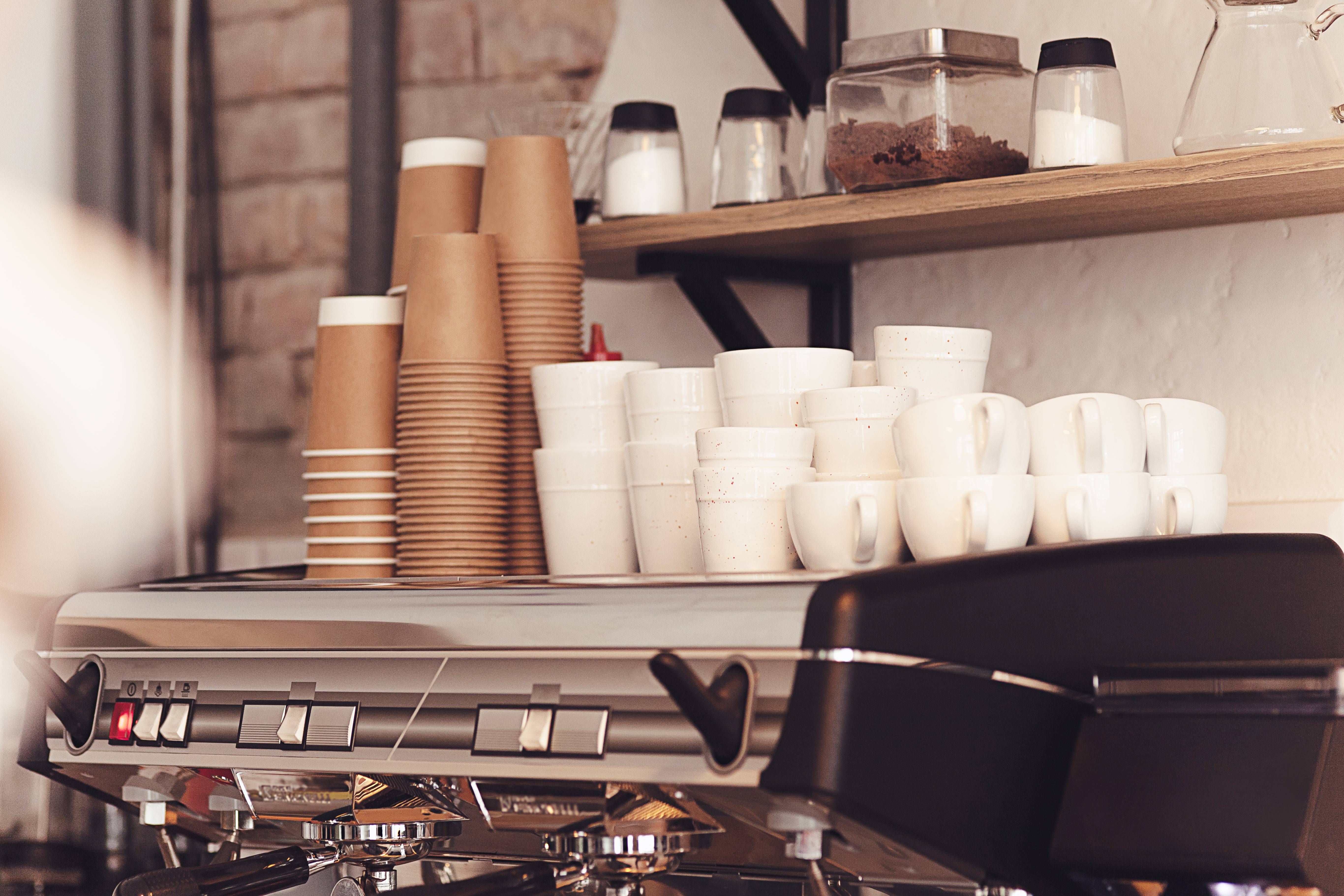Disposable coffee cups stacked on top of an espresso machine.