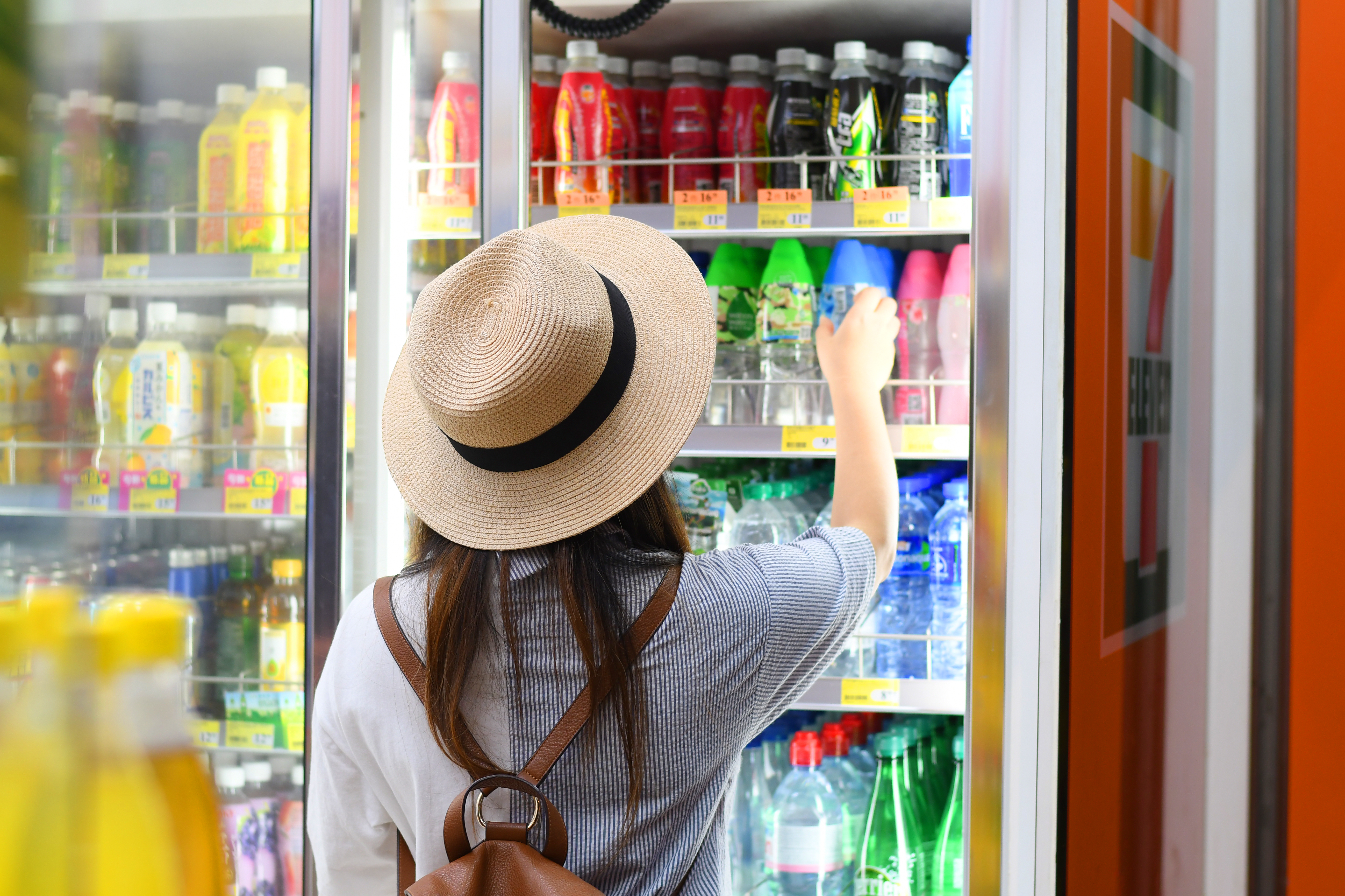 A woman standing in front of a refrigerator in a Chinese 7-Eleven